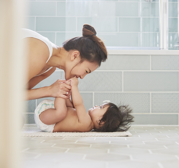Mother playfully holds baby daughter's feet up in the bathroom