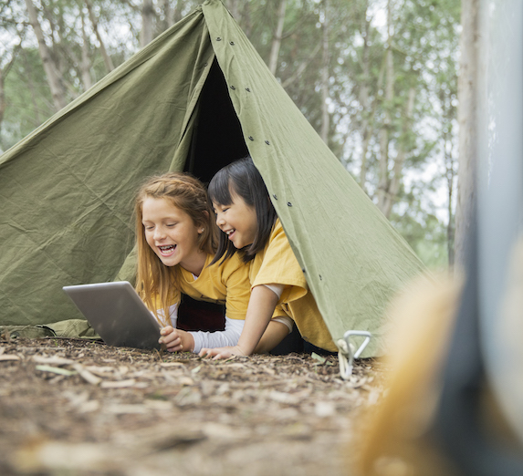 Young girls play on a tablet while lying in a tent outdoors