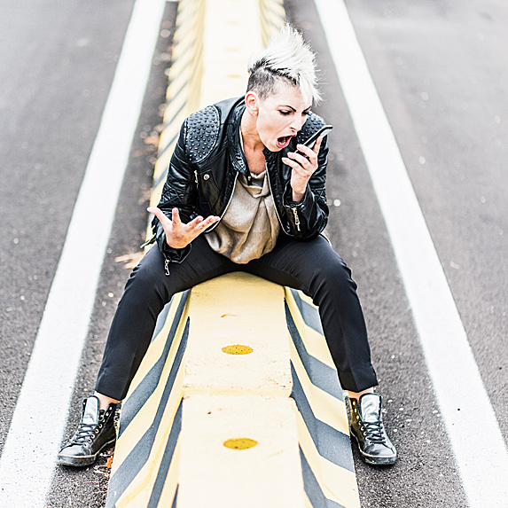 Woman in the middle of road, screaming into phone