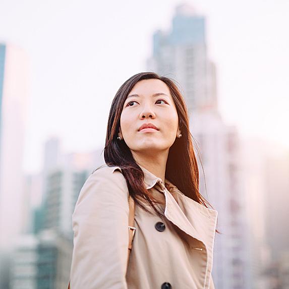 Woman on a big city street, looking hopeful