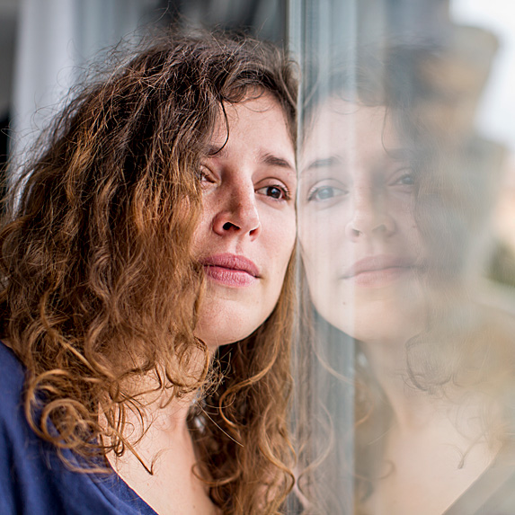 Upset woman leaning against window, staring out of it