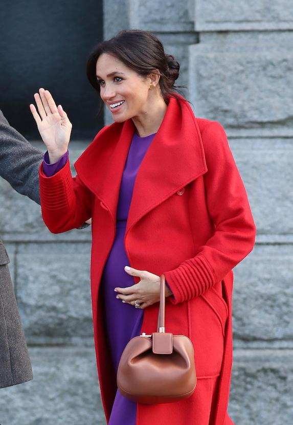 Meghan Markle wears a red coat and purple dress