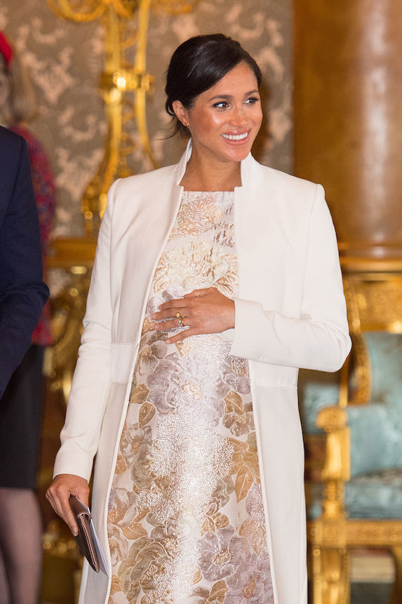 Meghan Markle wears a formal dress and overcoat