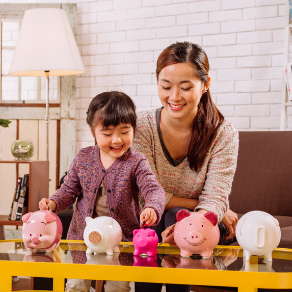 Woman with daughter and a row of piggy banks