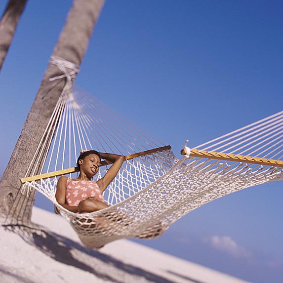 Woman sleeping in hammock on beach
