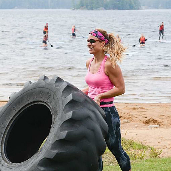 Woman flipping tractor tire on beach