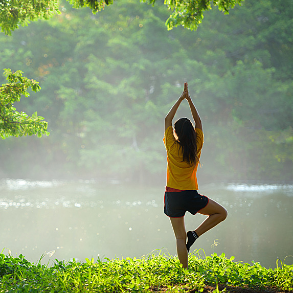 Woman doing yoga in lush landscape next to water