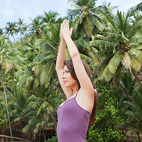 Woman doing yoga pose next to tropical trees