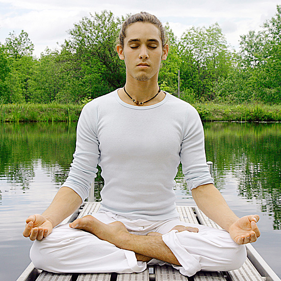 Man sitting on dock in yoga pose