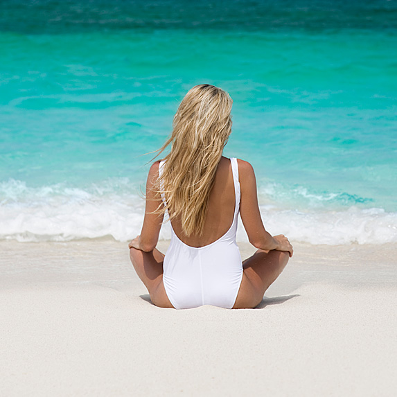 Rear view of woman in white swimsuit sitting crosslegged next to ocean