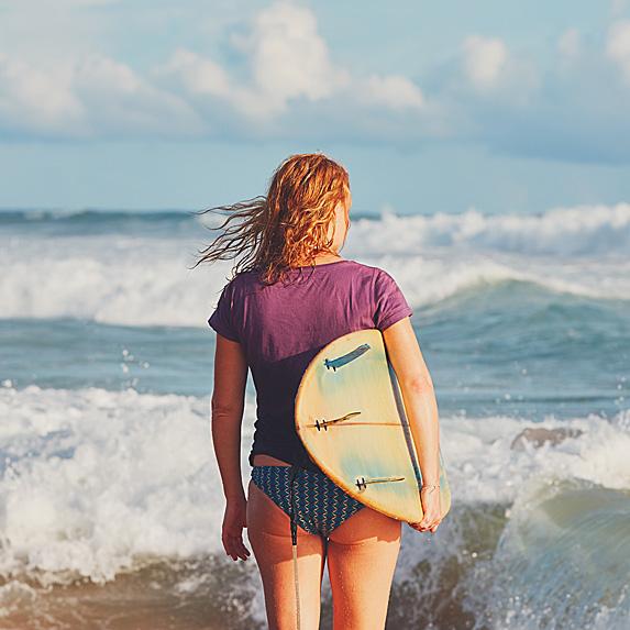 Woman holding surfboard walking towards ocean