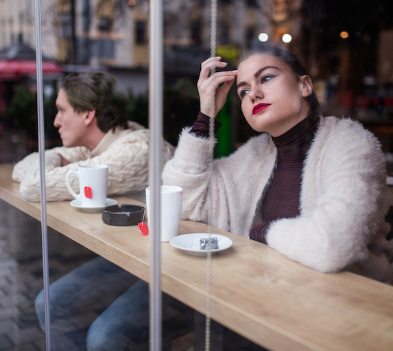 Unhappy couple sit apart at a café, not speaking