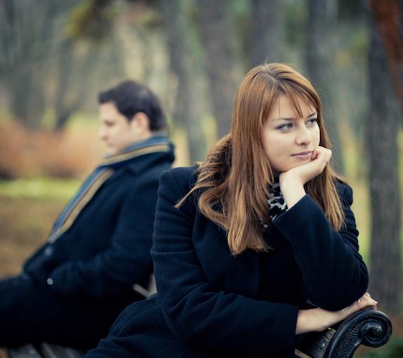 Unhappy couple sit apart on a park bench