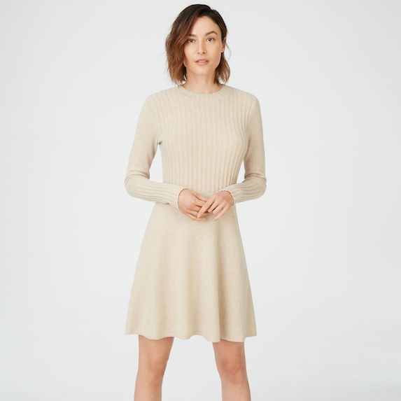 Model wears a cream-coloured knit mini dress