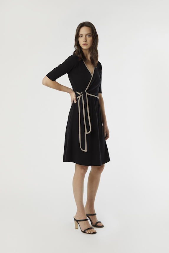 Model wears black wrap dress with brown trim detail