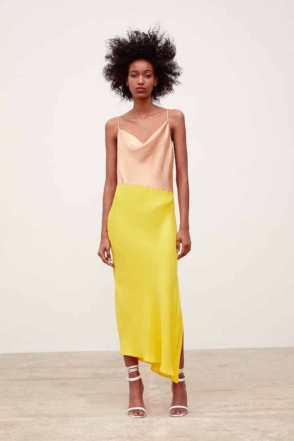 Model wears a satin slip dress in yellow and pink