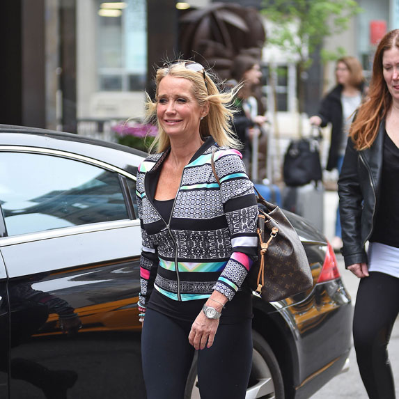 Kim Richards walking down the street smiling