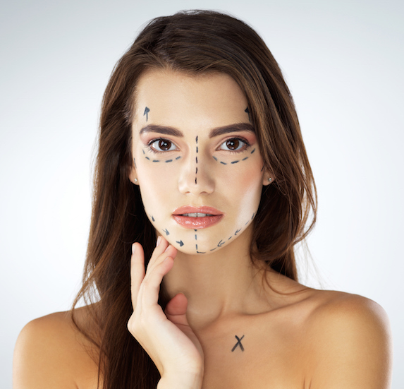 A beautiful young woman's face is mocked up with a marker for plastic surgery purposes
