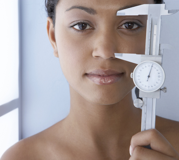 Beautiful woman holds a medical tool up to her face