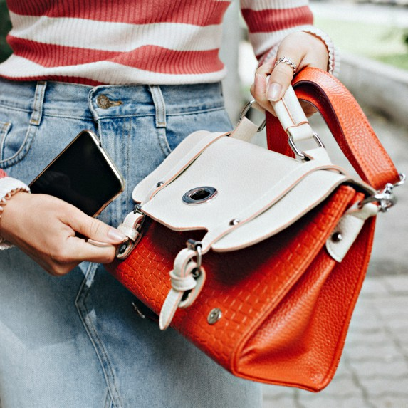 Woman puts her phone easily back into her purse