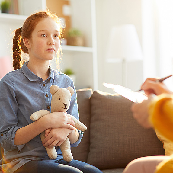 Nervous middle-school age girl looking holding teddy bear during counselling session