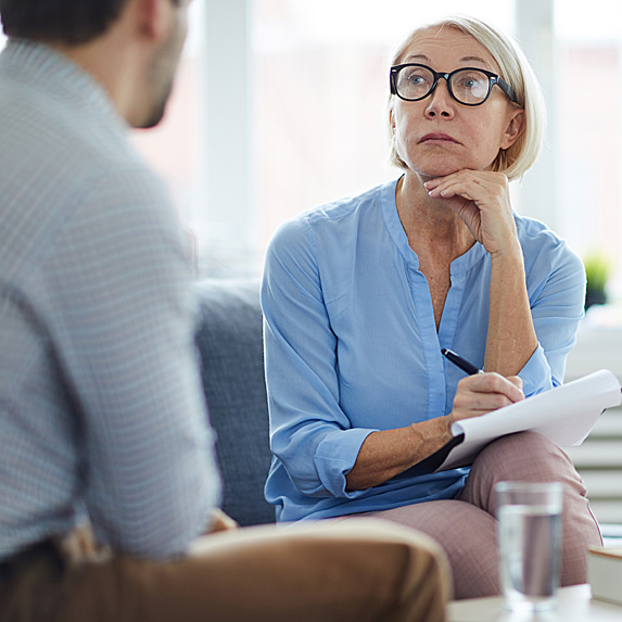 Man sitting across from older female therapist