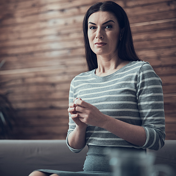 Nervous looking woman sitting on couch