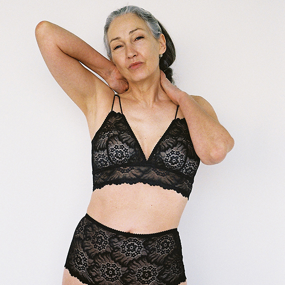 A woman with her arm wrapped around the back of her neck, wearing black lacy lingerie