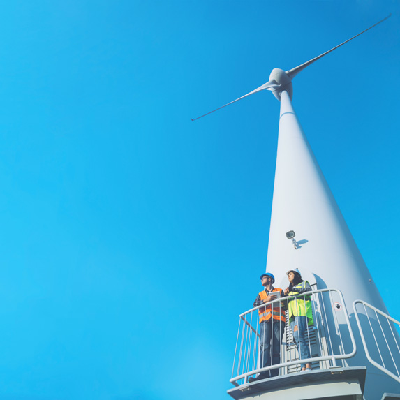 Technicians at the base of a wind turbine