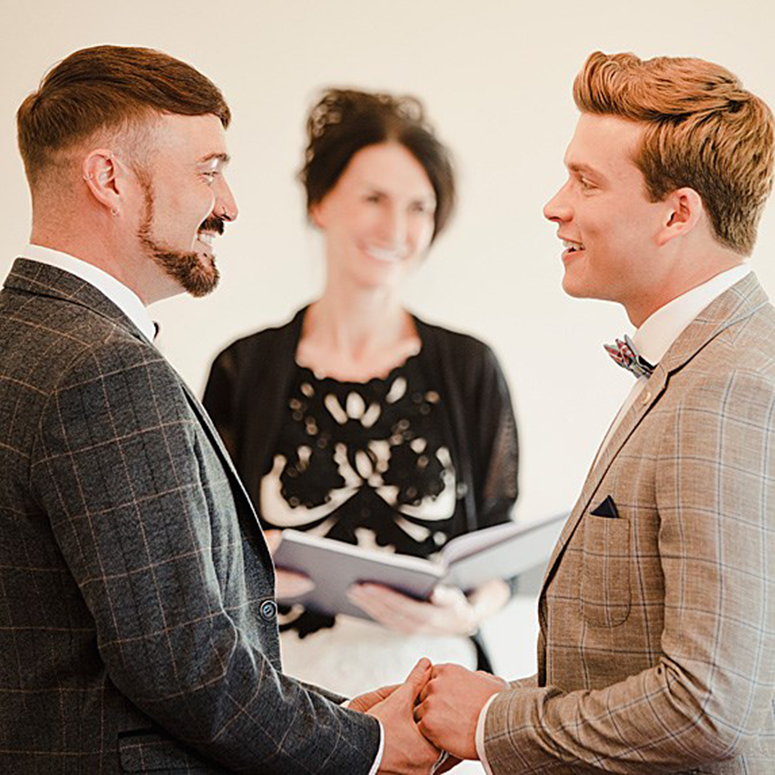 A queer male couple exchanging vows