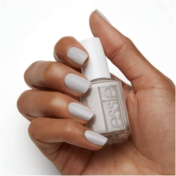Woman's hand holds a bottle of gray nail polish from Essie