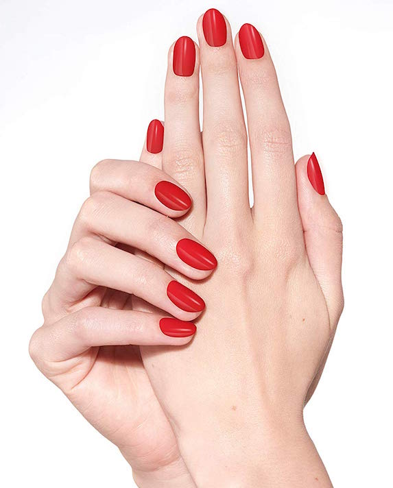 Women's hands featuring red nail polish from Sally Hansen