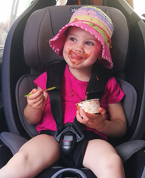 Messy toddler eating in car