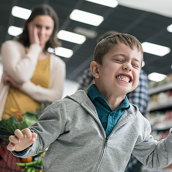 Boy screaming in grocery cart as embarrassed mom looks on