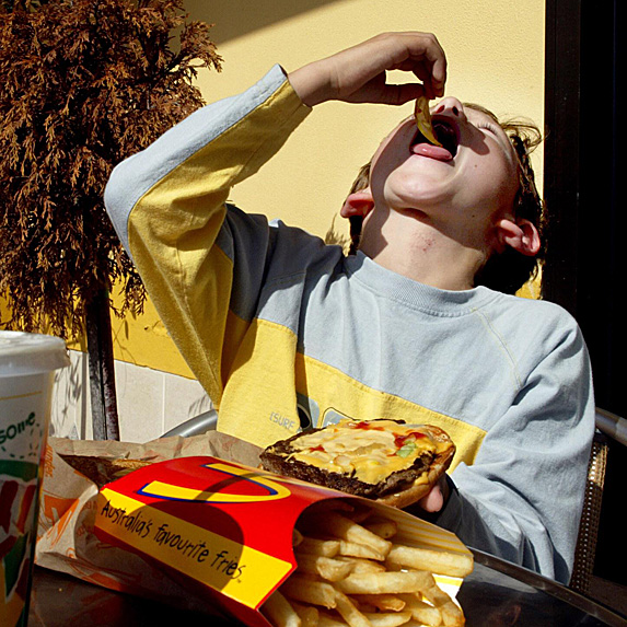 Boy scarfing down fries