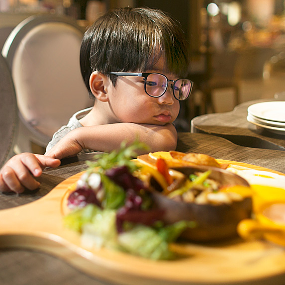 Boy sulking at table with full plate of food in front of him