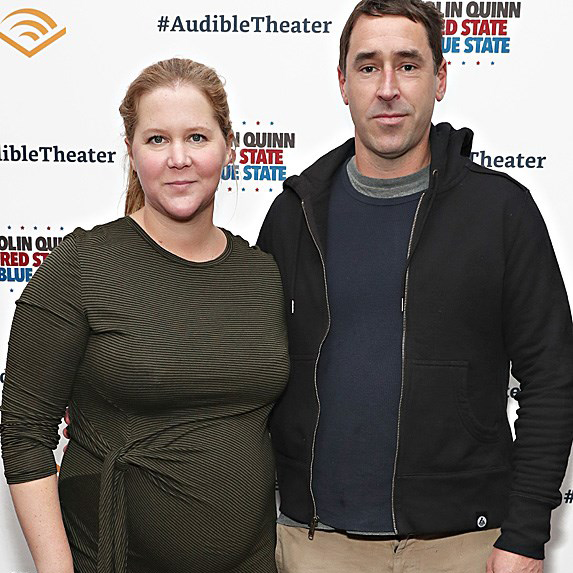 a pregnant Amy Schumer with husband Chris Fischer on the red carpet