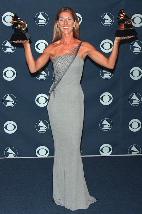 Celine Dion holds four awards as she poses for photos at the 1999 Grammy Awards
