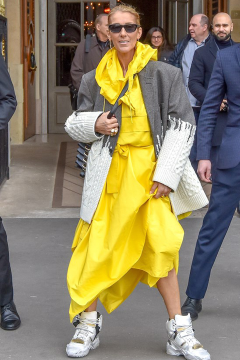 Celine Dion wears a yellow outfit and grey blazer in Paris in 2019