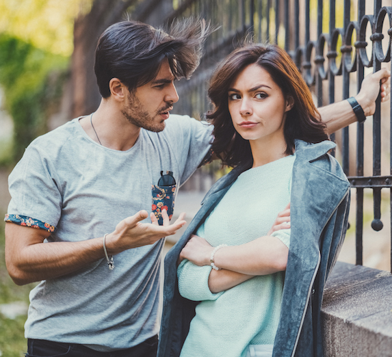 Woman looks skeptical as her partner talks to her outdoors
