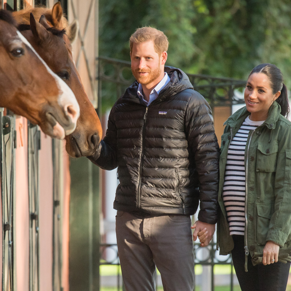 Meghan, Duchess of Sussex and Prince Harry visit a stable of horses.