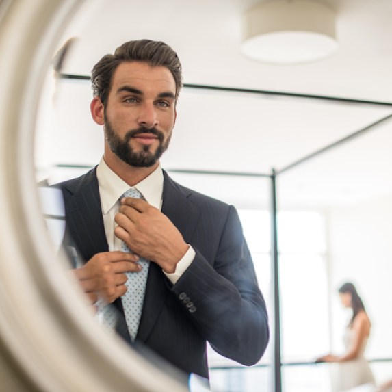 Man admires his appearance in the mirror and partner stands blurred in the background