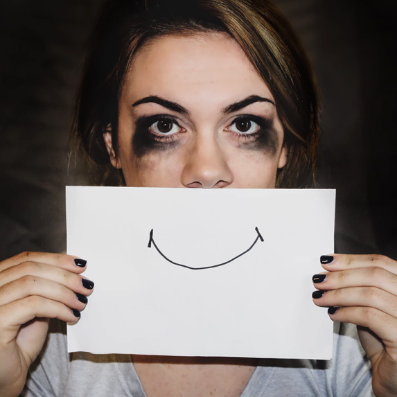 Emotional woman with pen drawn smile