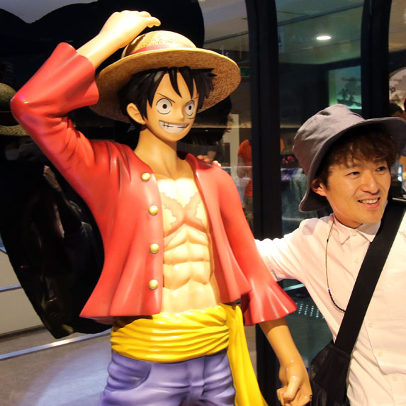 A fan poses with a statue of the manga character Monkey D. Luffy
