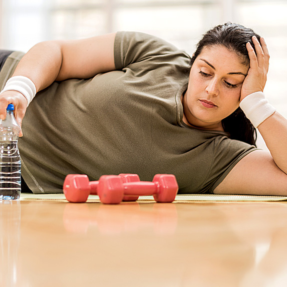 Woman lying on gym floor, looking forlornly at hand weights