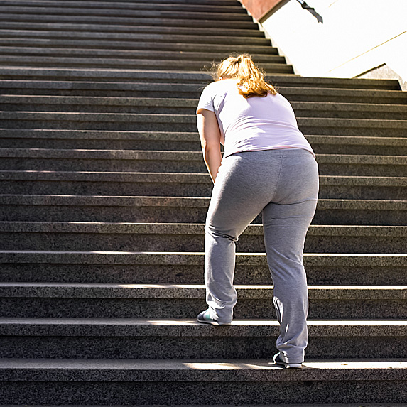 Rear view of out-of-shape woman climbing stairs