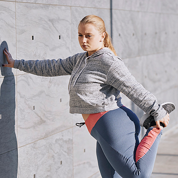 Woman leaning against wall and stretching hamstring