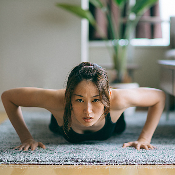 Woman doing pushups in living room