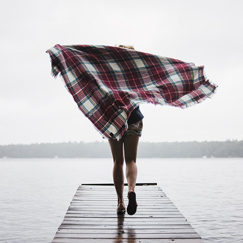 A woman running on a dock with a plaid blanket flowing behind her