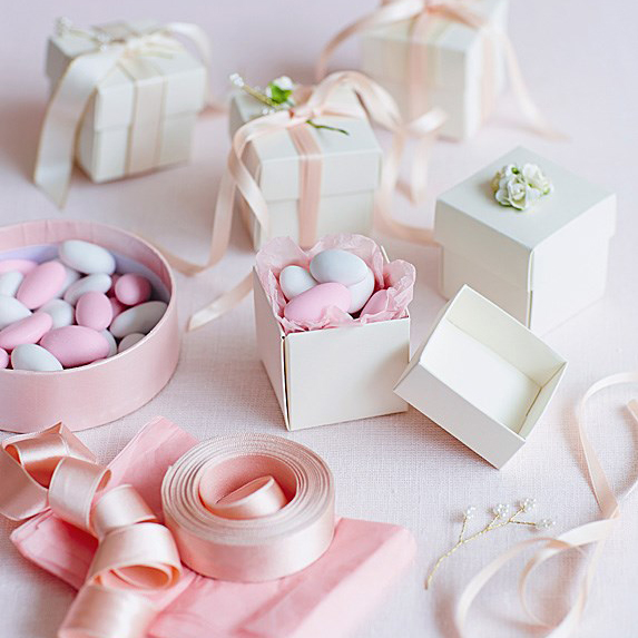 A closeup of wedding favours in boxes with bows